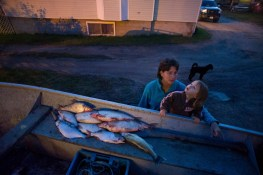 Dawn Ladouceur and her granddaughter gather around at boat of Dawn's husband Smokey to see his catch.