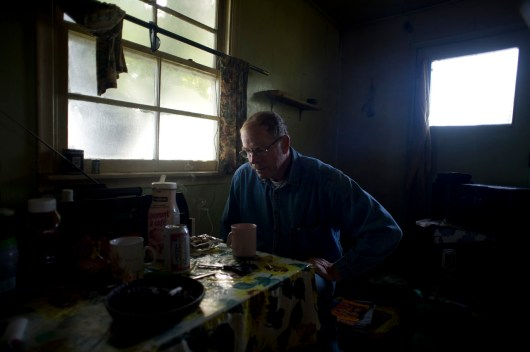 John Rigney sits down in a fur trapper's cabin in the Athabasca Delta.