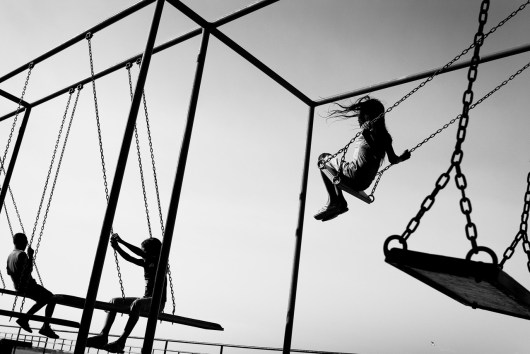 BRAZIL, SANTAREM. OCTOBER 2008. Daily life scene. children swinging in a playgraund