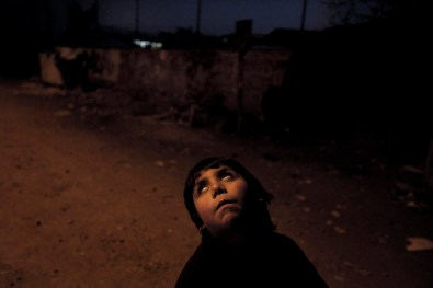 A boy walks playing through a dark passage in Puente Alto. It's common to see little kids alone in these vulnerable shantytowns in Santiago