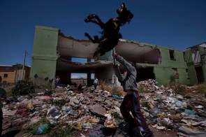 """A kid plays with a dog's carcass in the heart of his destroyed neighborhood. """"Villa El Volcán"""" (The Volcano shantytown) is an icon of Chile's social exclusion. Every winter the houses ended up flooded with the rain because of their deficient construction. Later, they discovered that the whole shantytown was b"""