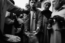 Pakistan, Rawalpindi District March 2009: Stuggle for food in the city, young man try to ask for a second portion of rice.