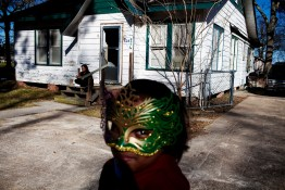 A masked girl watches the Mardi Gras parade pass by her home in Mamou, Louisiana on Tuesday, February 16, 2010.