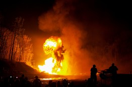 Diesel drums in cars explode after being shot with tracer bullets at the Knob Creek Machine Gun Night Shoot in West Point, Kentucky on April 9, 2011.