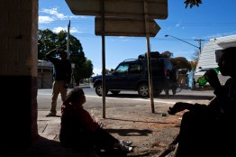 "Residents drink wine from plastic bottles on main street in Wilcannia as a caravan of tourists drive by. As one resident put it, many people are afraid to come to Wilcannia because ""you see the problems right there in your face"". David Maurice Smith/Oculi."