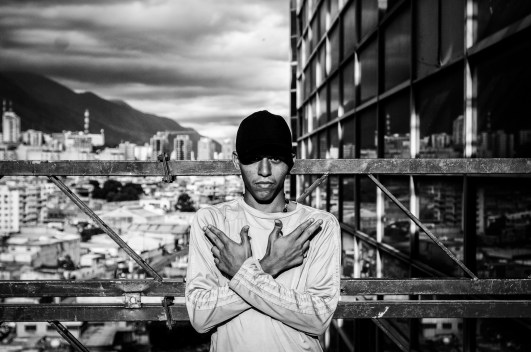 A boy makes the sign of a criminal gang while pose for a photo