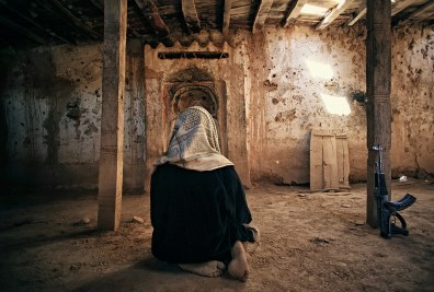 Shibam, Yemen: The boy that has leaned his rifle against the wall is praying in an old abandoned mosque in the desert, near the historical town in the Hadhramaut valley. © Matjaz Krivic