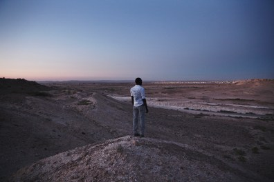 """Nouraldin, 26 years old, Overlooking the Negev desert and Holot Detention Centre. He has been in Israel for 6 years. He has been in Holot since March 9th. He is a refugee from Sudan, Darfur. """"Yesterday was the first time I ever lied to my mother. She asked me where I was, and I told her I was in Tel Aviv and everything is fine. She asked me why I was lying because she saw on the news in Sudan that they were putting Sudanese people in a prison. I have never lied to her before and I felt really bad about it."""""""