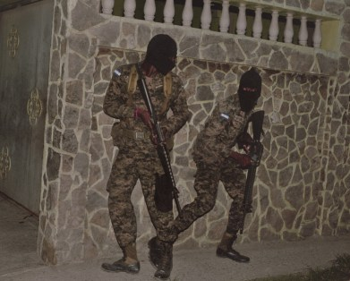 Honduran military engage gunmen who were hiding out inside a residence in San Pedro Sula. (Dominic Bracco II / Prime for Pulitzer Center on Crisis Reporting)