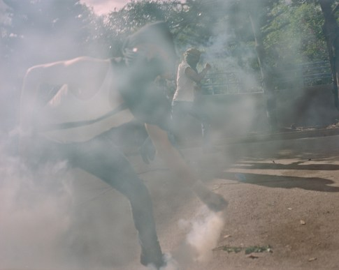 University students throw teargas bombs back at police during an anti fraud protest in Tegucigalpa. (Dominic Bracco II / Prime for Pulitzer Center on Crisis Reporting)