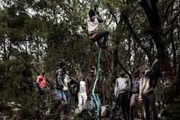 """Migrants from the Ivory Coast train climbing with a self-made rope and hook in the unofficial migrant camp on the Gorougou Hill overlooking the Spanish exclave Melilla from Nador, Morocco, July 2, 2014. The migrants are planning to storm the nearby three rows of fences that mark the border between Melilla and Morocco. They use self-made ladders and ropes such as the one pictured here. Hundreds, sometimes thousands of migrants wait on the hill, some up to a year. Over time, a well-defined social structure has evolved in the camp. There are clear borders between national communities within the camp and each community has a """"President"""" with a circle of advisers. To enter some communities, migrants have to pay an initial and a daily fee. Some are hierarchically and capitalist, some are more equal and socialist."""