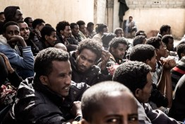 Eritrean refugees and migrants sit in a detention center during a roll call, Subrata, Libya, April 21, 2014. According to Italian officials, 600,000 migrants and refugees are currently waiting in Libya to cross the Mediterranean towards Europe.