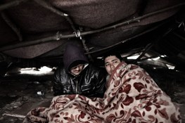 Zahir (left) and Khabir, illegal Afghan immigrants, wake up after a night in a makeshift tent that was partly destroyed by police a few nights earlier, Subotica, Serbia, Nov. 10, 2012. Zaher lost his legs below the knees. He says that Taliban cut them off. He made it to Serbia on crotches and one proestetic leg. Zaher says he is 16 and Habir 15 years-old. Many illegal immigrants try to get from Greece through the Balkans to northern parts of the European Union. Recently, Serbian police deported many refugees from here to Macedonia.