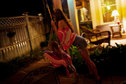 August Malouf pushes a little girl on a swing at a house party in Greenwood, Mississippi on May 20, 2012.