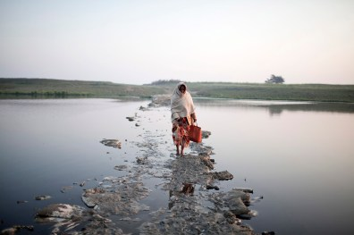 an eldery Woman crosses a small channel of the ganges on a submerging bridge made of waste, Feb 2014
