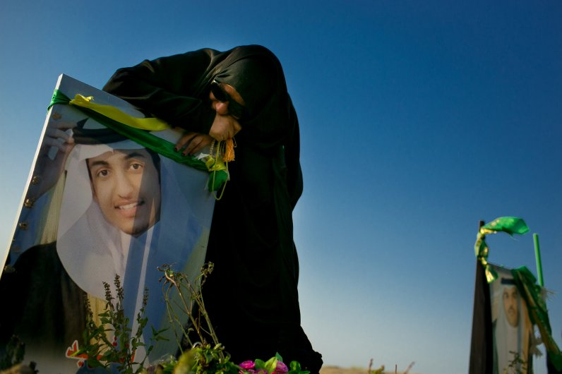 Um Tahir is surrounded by family and friends at the new cemetery. Only the bodies of the 4 men stand in the bare land.