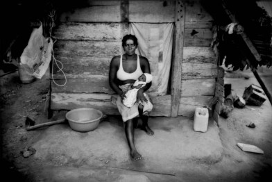 """Saamaka Maroon mother with her newborn child in front of her house in Ben Dikonde, near the village of Djumu, Boven Suriname (Upper Suriname River). Suriname. The Maroons, a general name derived from the Spanish, """"cimarron"""" used in Hispaniola to refer to escape cattle that took to the hills, are descendents of Africans who escaped slavery on foot centuries ago to live deep in the Amazon much as they had in the rainforests of West Africa. Maroons refer to themselves as """"Busikonde Sembe"""" or """"People of the Bush""""."""