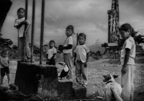 """""""Afectados"""" (Affected Ones): Oil derrick towers above students, with their pet toucan, in front of their elementary school, where they must endure the noise, noxious fumes and the dust raise by heavy trucks associated with the petroleum business. Near Dayuma along Via Auca. Ecuadorian Amazonas."""