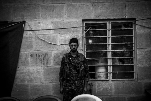 Iraq, Korsi - Sinjar Mountains: A PKK/YPG fighters posing against a wall in the village Korsi, behind him, he dashes scratched into the wall for every killed IS-fighter.