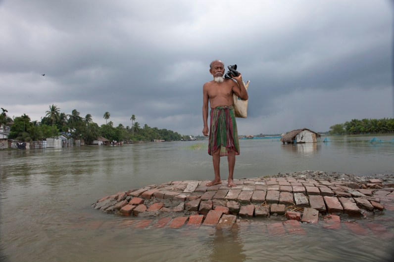 A flood-affected man stands on high land waits for a boat.