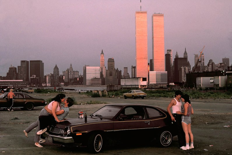 """""""I took the picture in the fall of 1983, at sunset at the old docks in New Jersey with a view towards the World Trade towers in New York City. I had heard that there was a traditional Lovers' Lane, a meeting place of young people in their cars, bringing booze and sometimes drugs. The sun was setting and the towers across the river were glowing before it became too dark to take more pictures."""" - Thomas Hoepker"""
