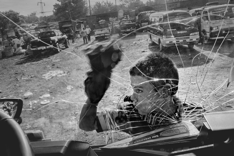 """Nicaragua, Managua, in tha market so named """"Mayoreo"""". A boy cleaning the windshields of cars for few pesos per day. In Central America and especially in Nicaragua, although compulsory education is planned up to 12 years, according to World Bank estimates, around 10% of children under 18 years living and working on the street. According to recent studies, approximately 320,000 children and young people between 5 and 14 years of age are forced to work."""