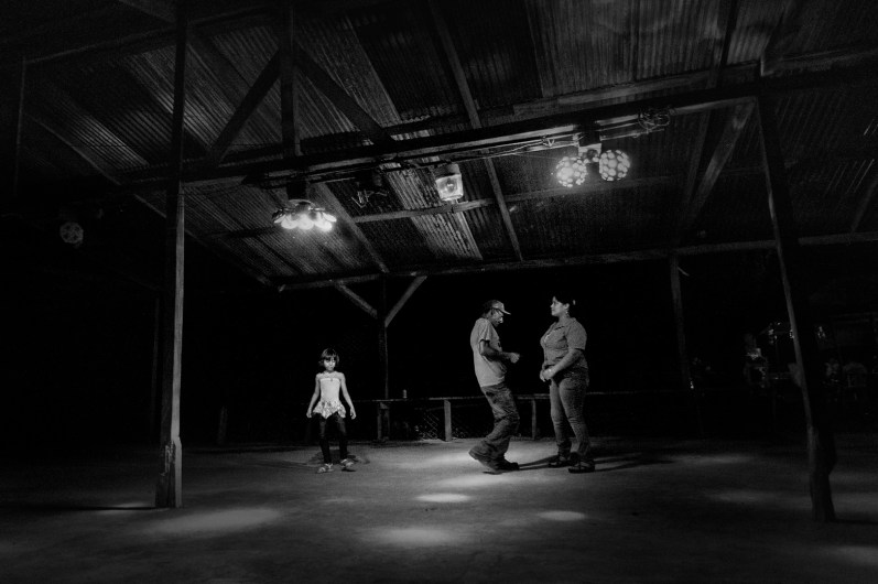 """Nicaragua, in a little village in the rural zone so called """"Los Guatuzos"""". Here a little girl with her parents in a disco of the village In rural areas, the destiny of the youngest includes their employment in agriculture, the main livelihood activities in this type of reality away from the big cities."""