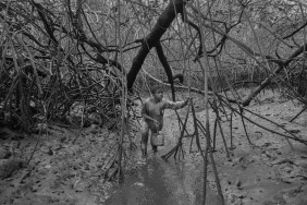 Alex Ocampo walks through a water inlet in the mangrove reserve. Shell pickers are used to work and walk waist deep in the mangrove. Most outsiders will invariably get stuck in the mud and have to get pulled out. Cayapas Mataje Reserve, Ecuador. 2014.