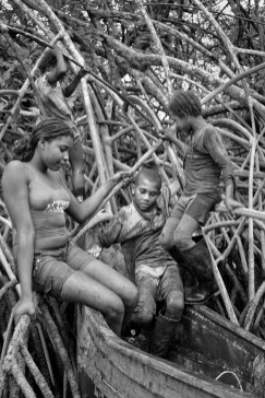 Children climb aboard a boat after a day of picking shells in the mud of the Cayapas Mataje Mangrove Reserve, 2009.