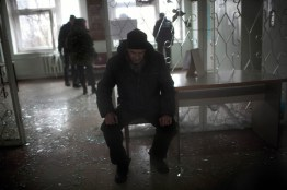 A patient of Donetsk hospital no. 3 sitting among glass debris , after the hospital was attacked by grad rockets.