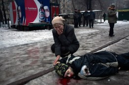 A mother holds her son's hand while mourning his death by a grad rocket attack in a residential area of Donetsk.