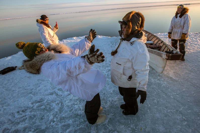 """Alaska High School Hall of Fame basketball coach Rex Rock wins a game of """"warmup"""" with young crew member Kaesyn Hill. Adam documents Jeremy Tooyak by the umiak. Changing ice conditions increasingly compel whalers to leave the umiak behind and hunt by motorboat. Tikigaq."""