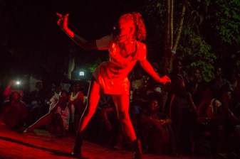 "A member of the LGBT community performs a dance for for those who have gathered in the courtyard of a ""secret"" location for the opening reception of Pride week. Kampala, Uganda. August 7, 2015. © Diana Zeyneb Alhindawi"