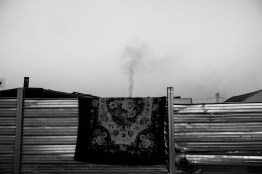 """A carpet hangs from the steel fence around the Roma camp. Behind it, in the distance, a column of black smoke is rising up. December, 15 2015 Masseria del Pozzo in Giugliano (NA) Roma from the camp in Masseria del Pozzo in Giugliano (NA) live differently from other Roma camps in Italy. The municipality of Naples allowed them to live in an authorized area, within the Land of fires, surrounded by highly contaminated dumps. Giugliano, a town of about 120,000 inhabitants, is in fact the heart of the so-called """"Land of fires"""" is an area in Campania, situated between the province of Caserta and the province of Naples, sadly known for being the most polluted area of this region, due to millions of toxic waste that have been illegally dumped here over the past 20 years. Half of the Roma living here are children and they are totally abandoned to themselves, without either the possibility to attend school or have a proper health assistance. Their playground is the dump; they wander and play and spend their days between toxic miasmas and industrial waste. I came across the scene while having a tour of the surroundings of Giugliano. I didn't influence the scene in any way."""