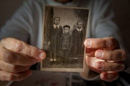 "Ion's wife, Nina, holds up a photo of Ion and his siblings that was taken in Siberia at the time of his deportation. While Ion successfully returned to Moldova, not all of his family was so lucky. Shortly before their return a younger brother of theirs died due to the extreme cold of Siberia and frailty of body that was a reality for many deportees at the time. Frequently, deportees talk about the small portions of bread and basic food they were given for their days' work, as well as the small salaries. This coupled with the intense cold of Siberia killed millions of deportees. It was not uncommon for deportees to sell precious family heirlooms for a bucket of potatoes or the like. Nina recalls one such episode where her mother sold off a family heirloom in exchange for a bucket of potatoes, ""[My mother left] with her carpet, a Moldavian carpet she wove by hand with a image of two flower baskets and she sold it when winter came because she had nothing to eat. So she sold that carpet [to a Russian] for a bucket of potatoes… I remember that we used to go to their house at nighttime when their lights where on and we could see the carpet through the window. It was so beautiful. I still remember it even though I was so little then. I remember its colors. My heart ached because it no longer belonged to us, because mother sold it for a bucket of potatoes."""