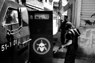 """Members of the BOPE (military police elite squad) enter their armored car during a Police operation in northern Rio de Janeiro. About 400 police officers invaded the Favela da Grota in Complexo do Alemao. Complexo do Alemao is considered the headquarters of one of the drug trafficking factions in Rio called """"Comando Vermelho"""" Red Command. In the operation, police confiscated assault riffles, an airstrike machine gun, several grenades and cocaine, cannabis and crack."""