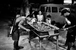 """A young man, known as """"Novinho"""" and involved with drug trafficking, plays foosball with an assault rifle on his back in Morro do Dendê, a favela where an estimated 50.000 people live in northern Rio de Janeiro. July 2008."""
