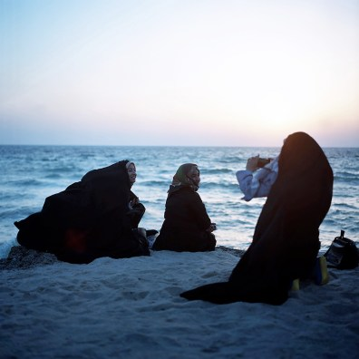 Down by the water, girls in chadors take pictures of each other at sunset on Kish island.
