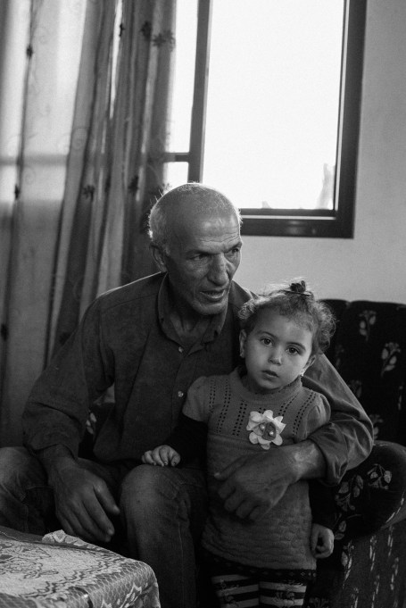 Khalil Zaanin is seen with his nephew Meera in his home in Beit Hanoun, northern Gaza, Palestine, on Oct. 28th 2014. Khalil Zaanin's farm was hit several times by an F-16 missiles and bulldozed completely by the Israeli army, during the war in 2014. His water well was destroyed and it took him a month to repair it.