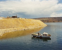 A man is paddling in a boat across the Keban Lake in eastern Anatolia. The Keban Dam was the first and uppermost of several large scale hydroelectric dam to be built on the Euphrates by Turkey. Although the Dam was not originally constructed as a part of the Southeastern Anatolia Project (GAP), it is now a fully integrated component of the project, which aims to stimulate economic development in Southeastern Turkey. Keban Dam Lake, reservoir created by the Keban Dam is reputedly the fourth-largest lake in Turkey after Lake Van, Lake Tuz and the reservoir created by the Atatürk Dam. Keban, Turkey