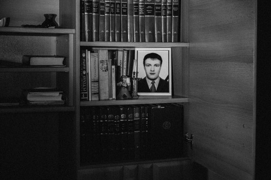 "Cupboard in the livingroom of Eugenija. When Eugenija opens one door she could see one picture of her dead son Petras. He commited suicide. She wrote down: ""Don't be alone, we're all from one and the same world. May no one take their own life voluntarily, because life is a gift."" Panevėžys, 1st of March 2018."