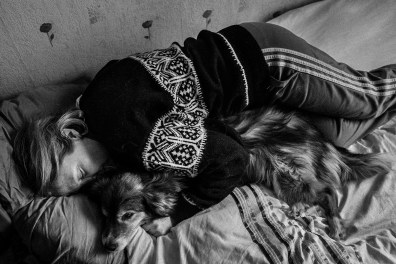 "Portrait of Donata with her dog Mikutis in bed. Donata has suffered from depression 18 years ago, during and after the divorce from her then-husband. Her dog has been helpful to her to leave the bed every morning in order to go for walks with him, Lithuania, Kupiskis, 30th of January 2016. Donata wrote: ""I thank Mikutis for bringing life back to me, and for the immense love he gave us. For sixteen years, we all shared daily life and festive moments, we grew, we lived, we learned. Mikutis is now in the hunting grounds of eternity, and we carry on living. My daughter studies at a university, I work and have her back, as the dog used to have our back at a certain point in time. It never asked questions, it never said anything, it never judged, only cuddled up to me and warmed me until all 'ice' melted."""