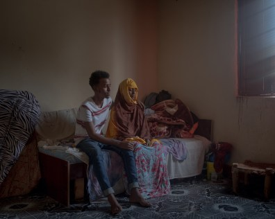 Abdizamad (19) poses together with his mother Qali Rooble (50) in their room in Hargeisa, Somaliland. Abdizamad began his journey to Europe in July 2017 without telling his mother. He paid smugglers who gave him instructions by telephone, guided him through Ethiopia to Sudan and from there to Libya. In Libya, he was kidnapped, beaten and held in a house with other refugees. The traffickers demanded a ransom of 5500 dollars from his family. 15 of his family members joined forces and bought him free after five months. Abdizamad got on a boat that was supposed to take him across the Mediterranean to Europe after all. After two days at sea, the refugees were taken on board of an NGO ship and brought back to Libya. There he was detained for three months and then returned to Hargeisa. His family raised 2,000 dollars and he opened a small shop. Many of the young people in Somaliland do not see any perspective in their homeland. Unemployment, poverty and the hope for a better life drive them into the arms of the traffickers on their way to Europe.