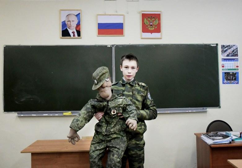 """Jeune cadet devant le drapeau russe et le portrait du président Poutine à l'école n°18, Serguey Posad. Parallèlement aux cours """"classiques"""", le directeur de l'établissement a décidé de créer des classes d'éducation militaire et patriotique."""