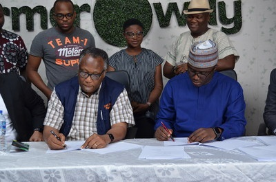 Best Foods chairman Emmanuel Ijewere and Founder and CEO of Farmcrowdy, Onyeka Akumah signing the acquisition deal at the Farmcrowdy office in Lagos