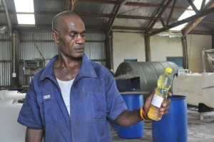 Iowane Bale, mill manager of the Koro biofuel mill holds a sample of the filtered oil. Credit: UNDP