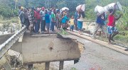 Locals cross the over flooded Bena Bridge. Credit: The National