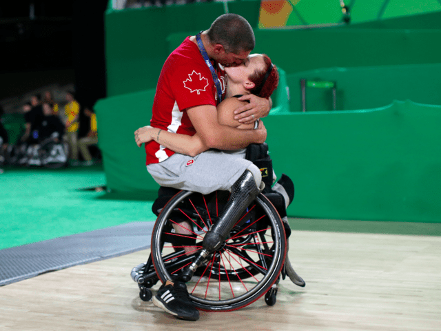 Canada's men's wheelchair basketball team player Adam Lancia kisses his wife Jamey Jewells of Canada after her match at the Rio Paralympics.