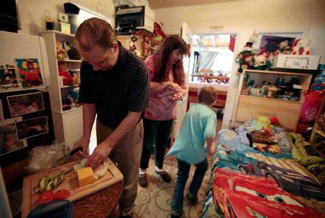 The Burger family from Los Angeles, California, gets ready in a converted garage in wife Elizabeth Burger's mother's home. The family lost their home in 2009 and was forced to sell their possessions.