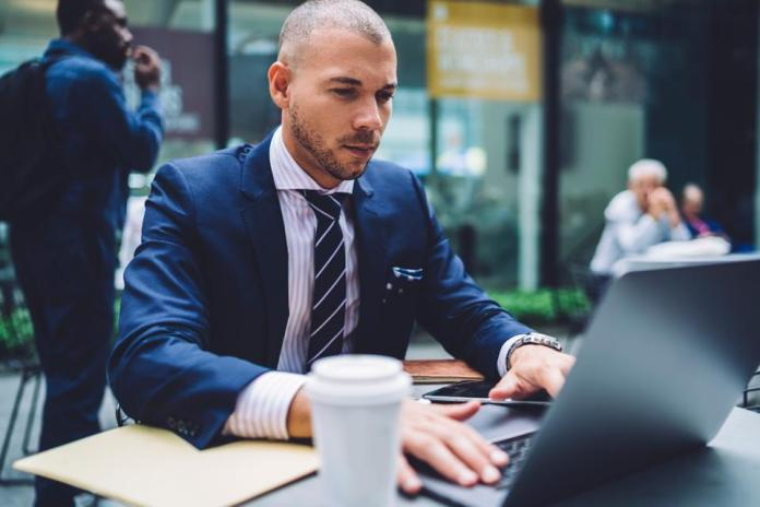 Caucasian businessman concentrated on accountings using application on laptop while sitting on cafe terrace, confident male lawyer in formal wear solving problem with project doing remote job